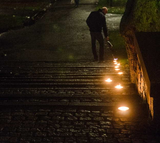"Man lighting tea lights, ""bringing light to darkness"", downtown Stockholm. Photo credits: Jonathan Luedee."